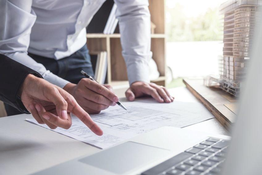 proyecto-arquitectura-retail-mesa-trabajo-personas-laptop-planos-boligrafo